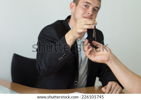 Young Male Real Estate Agent Giving the House Key to the Buyer While Looking at the Camera. - stock photo