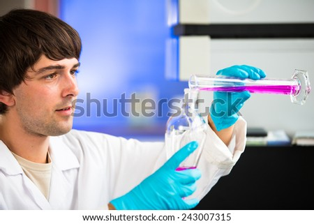 Young male researcher carrying out scientific research in a lab (shallow DOF; color toned image) - stock photo