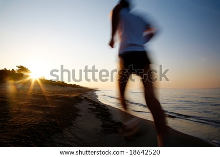 Young male runner running on a empty beach at dawn. Blur effect. - stock photo