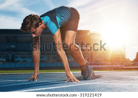 Young male runner taking ready to start position against bright sunlight. Sprinter on starting block of a racetrack in athletics stadium. - stock photo