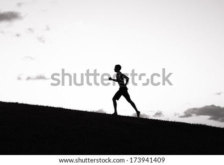 Young male running on a road during sunset.