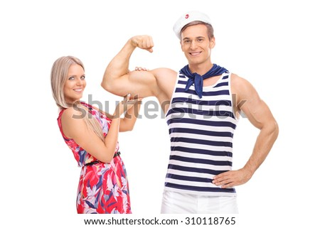 Young male sailor flexing his bicep and his girlfriend posing with him isolated on white background - stock photo