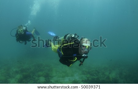 young male scuba diver swims over reef