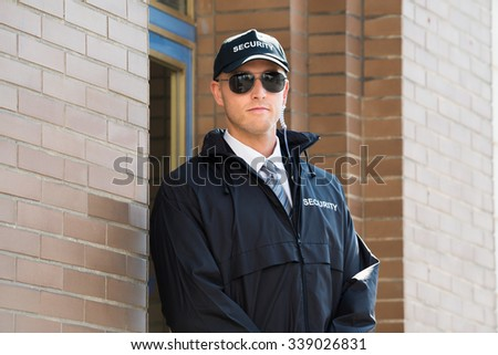 Young Male Security Guard Standing At The Entrance - stock photo