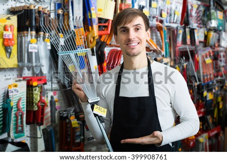 Young male seller smiling at gardening section of household