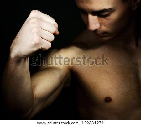 Young male showing biceps and fist - stock photo