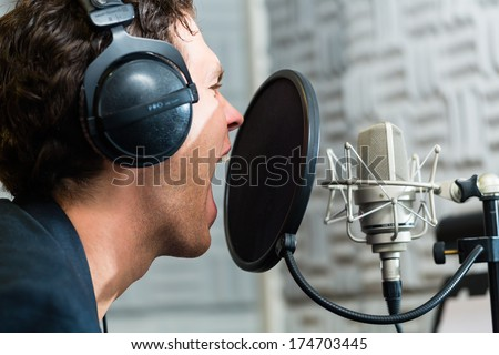 Young male singer or musician with microphone and headphone for audio recording in the Studio - stock photo