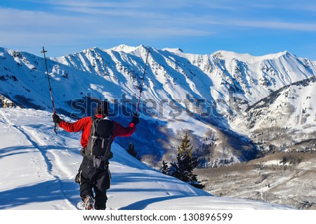 young male ski touring in colorado mountains saluting the mountains with his ski poles