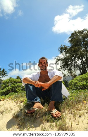 young male smiling and sitting on a hill by the beach - stock photo