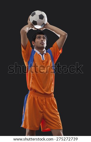 Young male soccer player throwing ball isolated over black background - stock photo