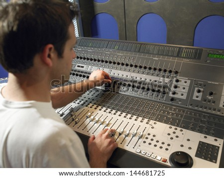 Young male sound technician in recording studio - stock photo