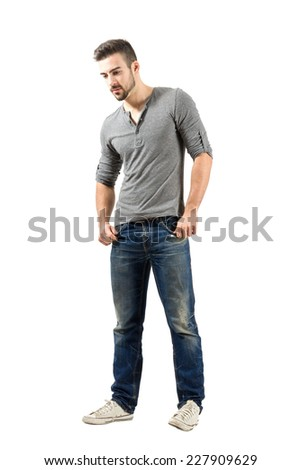 Young male standing looking down. Full body length portrait isolated over white background. - stock photo