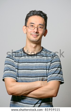 Young male standing with folded hands against gray wall - stock photo