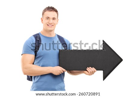 Young male student holding a big black arrow pointing right isolated on white background - stock photo