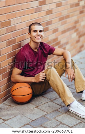 young male student holding basketball,sitting against brick wall, smiling, variation - stock photo