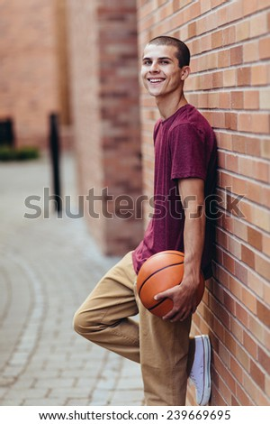 young male student holding basketball, smiling, leaning against brick wall - stock photo