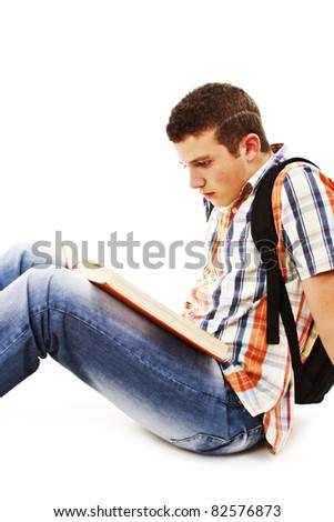 Young male student is sitting on the floor, reading a book. All on white background.