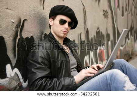 young male student  sit laptop outdoor silver graffiti wall - stock photo