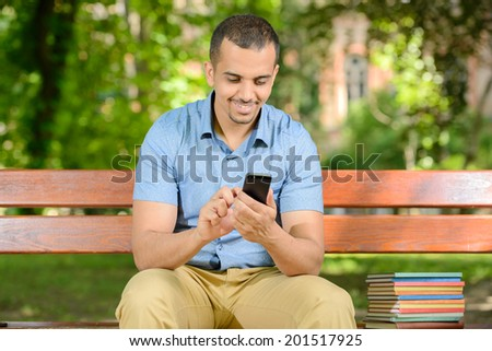 Young male student using a smartphone outdoors in park - stock photo
