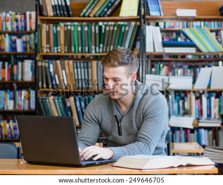 Young male student using laptop in the university library - stock photo