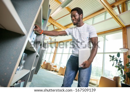 Young male student with digital tablet selecting book in library - stock photo