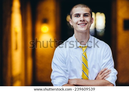 young male student, with tie, smiling, arms folded, horizontal - stock photo