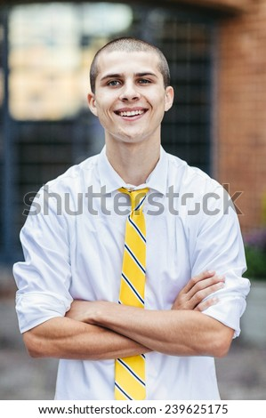 young male student, with tie, smiling, background blurred, arms folded - stock photo