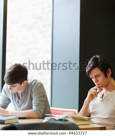 Young male students working in the library - stock photo