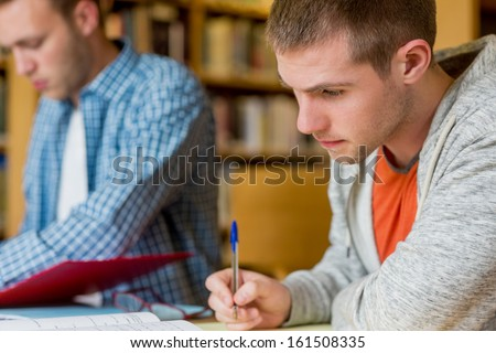 Young male students writing notes at desk in the college library - stock photo