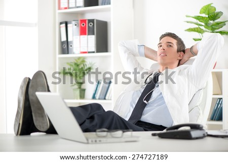 Young male successful doctor in the doctor's room sitting on chair, hands behind  head with her feet up on a desk. He is relaxing and daydreaming. - stock photo