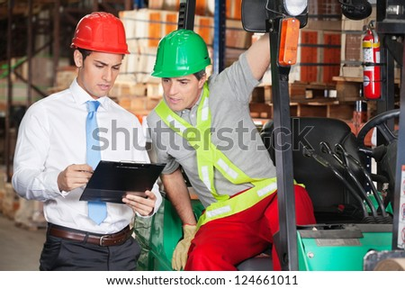 Young male supervisor showing clipboard to forklift driver at warehouse - stock photo