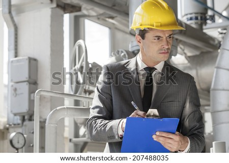 Young male supervisor writing on clipboard in industry