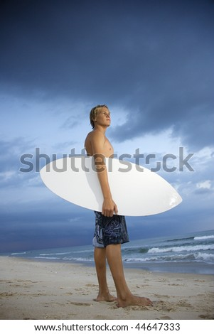 Young male surfer standing on beach with surfboard looking out at ocean. - stock photo