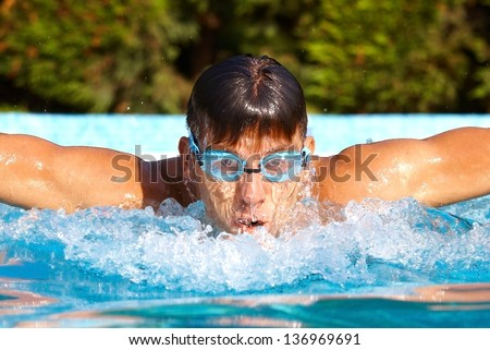 Young male swimmer in swimming pool at summertime, butterfly stroke.