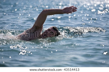 young male swimmer swimming in the sea/ocean - stock photo