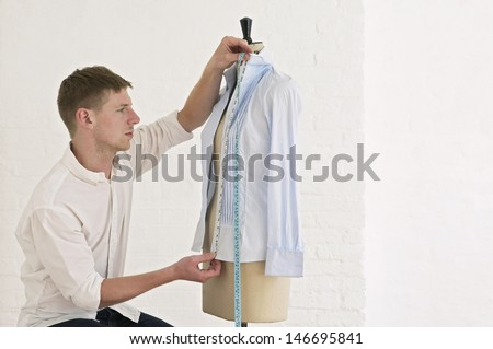 Young male tailor measuring shirt on dressmaker's model in fashion studio