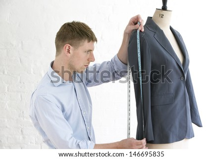 Young male tailor measuring suit on mannequin in fashion studio