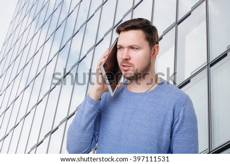 young male talking on the digital tablet  - stock photo
