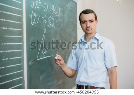 Young male teacher or student holding chalk writing on chalkboard in classroom - stock photo