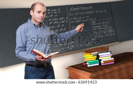 Young male teacher pointing to the blackboard in a maths classroom - stock photo