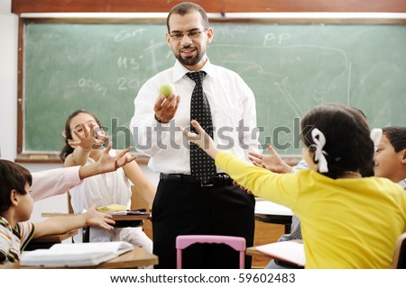 Young male teacher with children in modern school, activities - stock photo