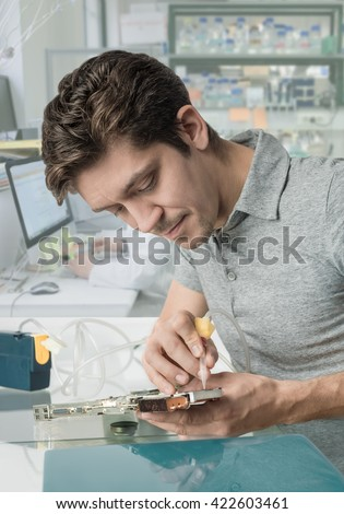 Young male tech with curly brown hair works in in research facility - stock photo