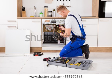 Young Male Technician Checking Dishwasher With Digital Multimeter In Kitchen