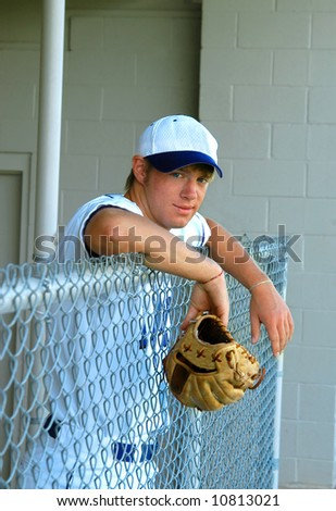 Young male teen hangs over the dugout fence holding his baseball glove.  White uniform. - stock photo