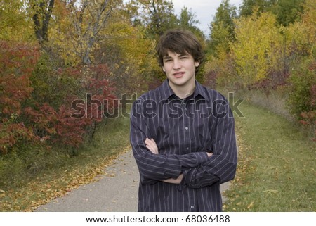 Young male teen standing on park trail with arms folded and colorful autumn leaves in background