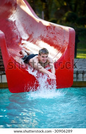Young male teenager having fun on a water slide