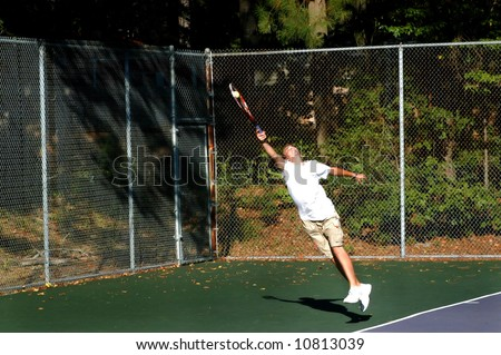 Young male tennis player gives extreme effort and returns a high tennis ball.  Feet are off ground and his stretch is to his limit. - stock photo
