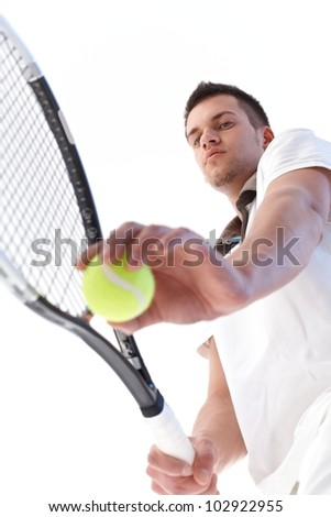 Young male tennis player preparing for serve, concentrating. - stock photo