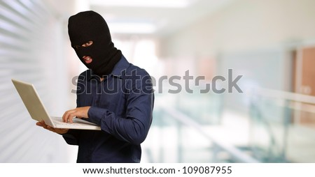 young male thief holding laptop, indoor - stock photo