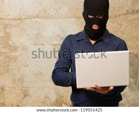 young male thief holding laptop, outdoor - stock photo